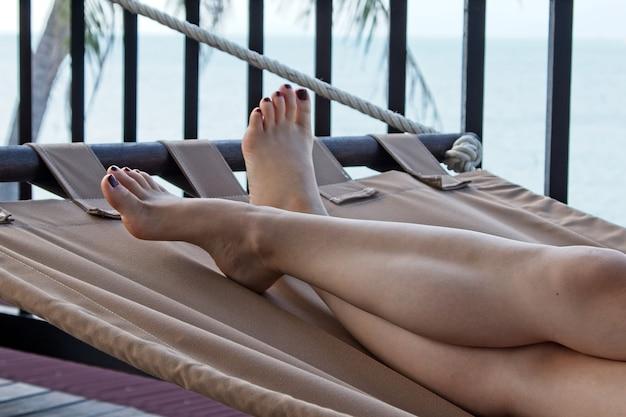 Foto de baixo ângulo de uma mulher branca relaxando na praia em um dia quente de verão
