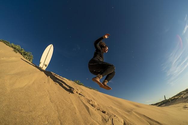 Foto de baixo ângulo de uma mulher pulando em uma colina arenosa com uma prancha de surfe ao lado