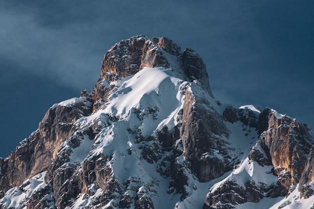 Foto de baixo ângulo de uma parte de uma cordilheira e um céu azul no inverno