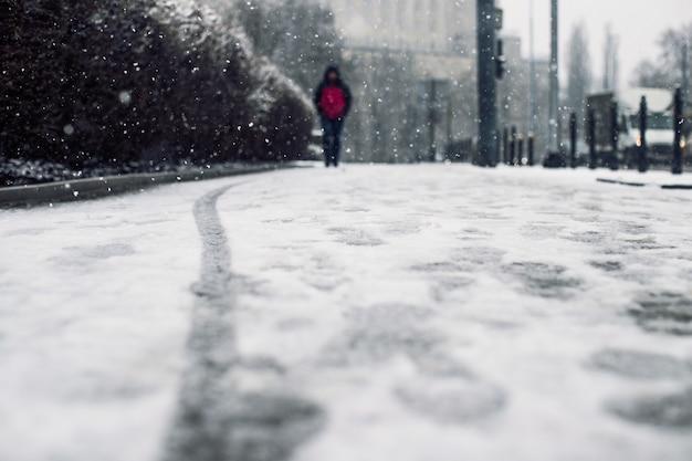 Foto de baixo ângulo de uma pessoa caminhando na calçada coberta de neve sob a neve