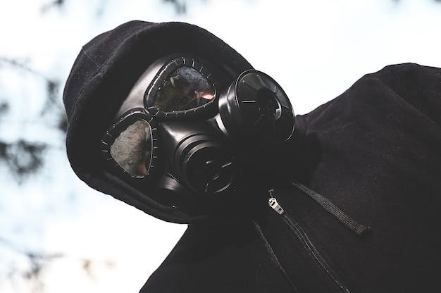 Foto de baixo ângulo de uma pessoa usando uma máscara de gás e jaqueta preta no rancho durante uma quarentena