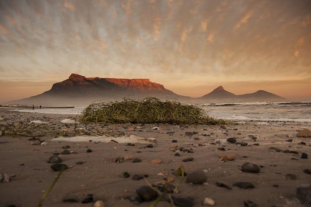 Foto de baixo ângulo de uma praia suja com um penhasco ao fundo em um dia nublado