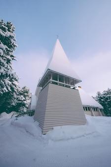 Foto de baixo ângulo de uma torre de capela coberta com neve espessa no inverno