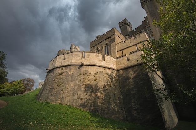 Foto de baixo ângulo do castelo e da catedral de arundel cercada por uma bela folhagem