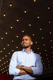 Foto de baixo ângulo do empresário africano negro bonito ao ar livre na cidade durante o verão, sorrindo e pensando.