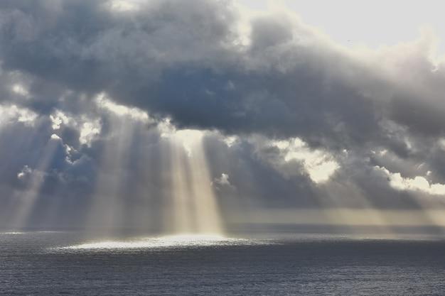 Foto de baixo ângulo do sol brilhando através das nuvens sobre o lindo oceano