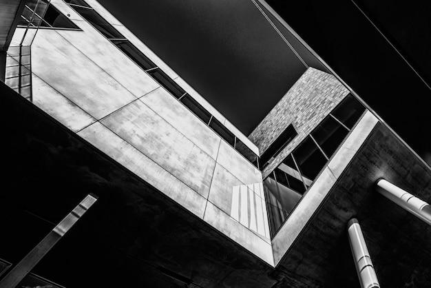 Foto de baixo ângulo em tons de cinza de um edifício com design interessante