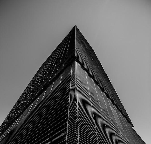 Foto de baixo ângulo em tons de cinza de um prédio comercial