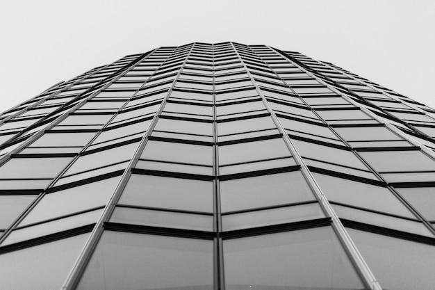 Foto de baixo ângulo em tons de cinza de uma construção de vidro