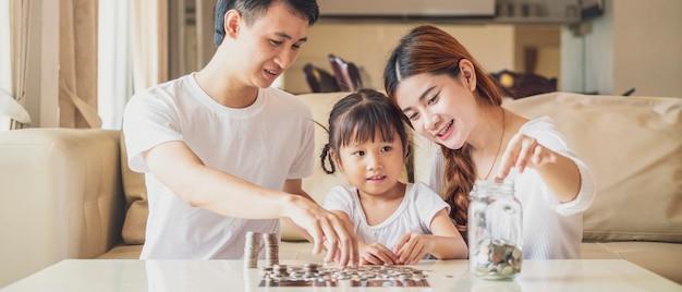 Foto de banner de família asiática ensina sua filha a economizar dinheiro colocando moedas no banco de vidro.