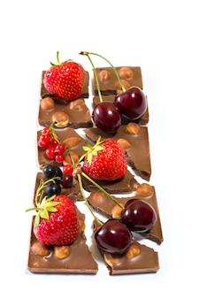 Foto de barra de chocolate quebrada com nozes e frutas isoladas