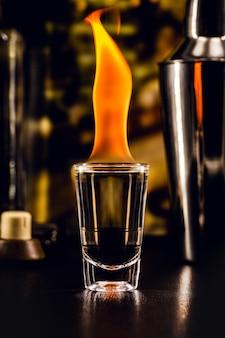 Foto de bebida quente de tequila, dose de bebida alcoólica com fogo, ambiente de bar