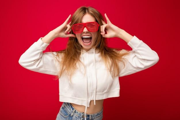 Foto de bela jovem loira positiva vestindo roupas casuais e óculos ópticos elegantes, isolados sobre a parede de fundo colorido, olhando para a câmera e se divertindo.