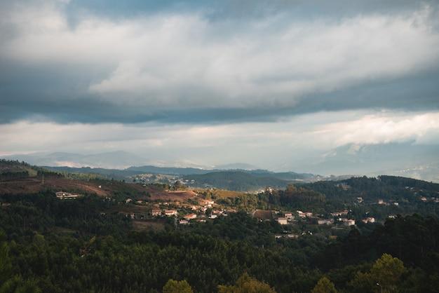 Foto de bela paisagem de uma cidade escondida entre as árvores em uma área montanhosa