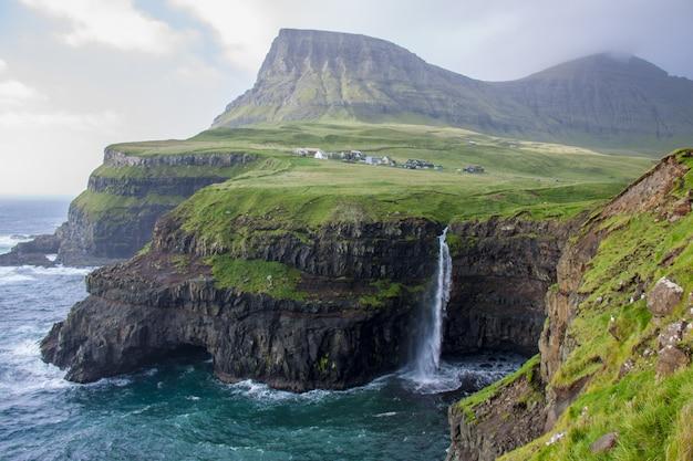 Foto de bela paisagem de uma costa rochosa coberta de vegetação ao lado de um corpo de água