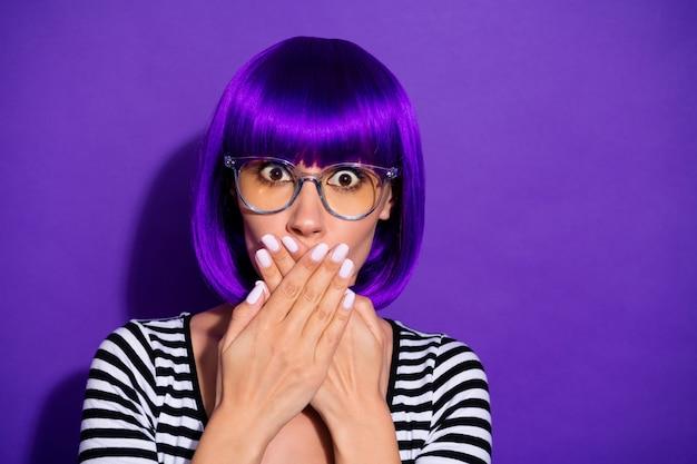 Foto de bela senhora cometeu um erro e falhou esconder a boca aberta com as mãos e usar peruca pulôver listrado isolado fundo roxo