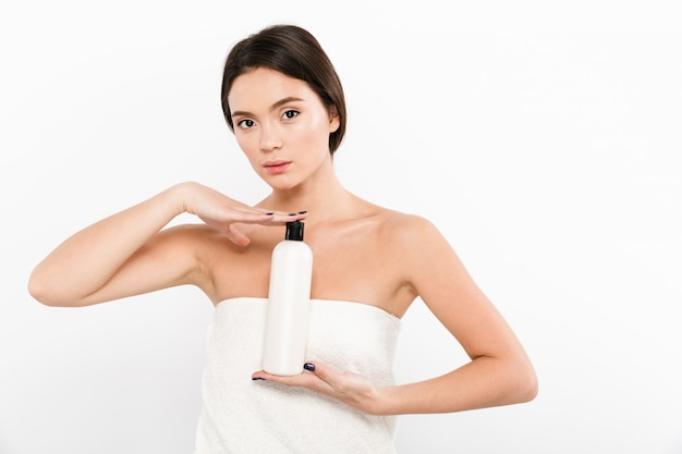Foto de beleza da jovem mulher asiática em toalha segurando a garrafa com creme hidratante ou óleo nas mãos, isolado sobre o branco