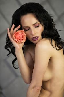 Foto de beleza de mulher morena glamourosa de olhos fechados posando de topless com uma rosa