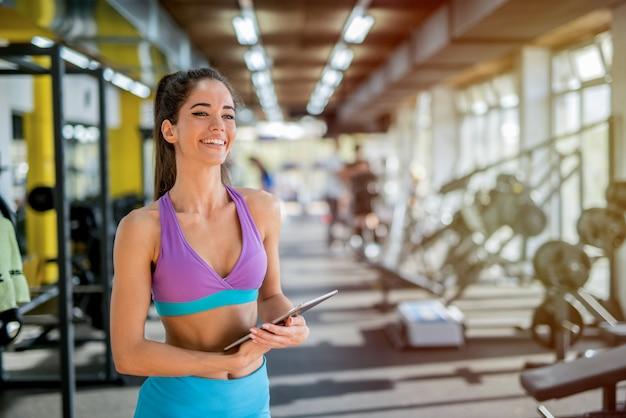 Foto de belo ajuste desportivo feminino personal trainer, posando em frente à câmera no brilhante ginásio.