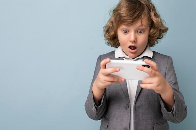 Foto de belo menino emocional chocado com cabelo encaracolado, vestindo um terno cinza, segurando e usando o telefone isolado sobre um fundo azul, olhando para um smartphone jogando jogos