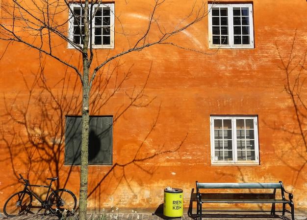Foto de bicicleta, banco, caixa e uma árvore nua ao lado de um prédio de tijolos