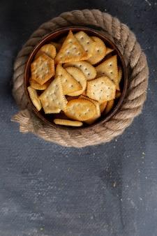 Foto de biscoitos salgados saborosos com cordas na mesa cinza