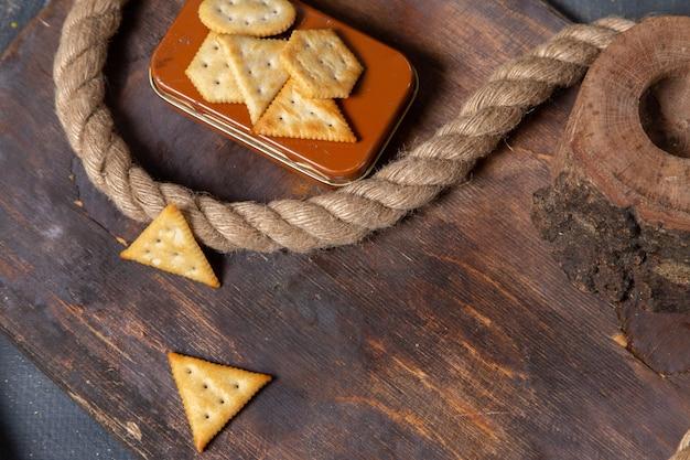 Foto de biscoitos salgados saborosos com cordas na mesa de madeira