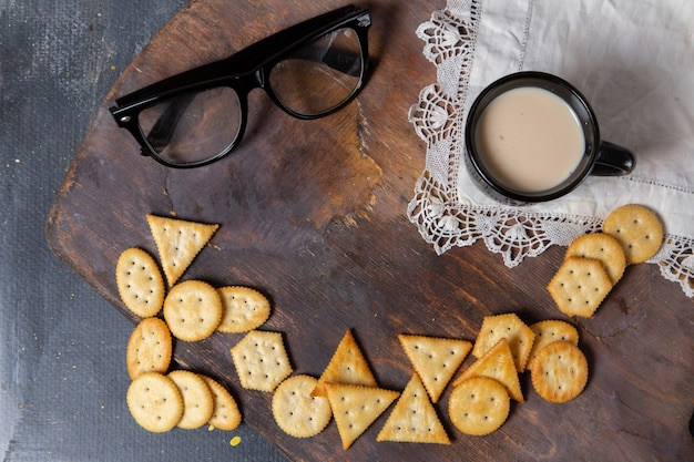 Foto de biscoitos salgados saborosos com óculos escuros e copo de leite na mesa de madeira