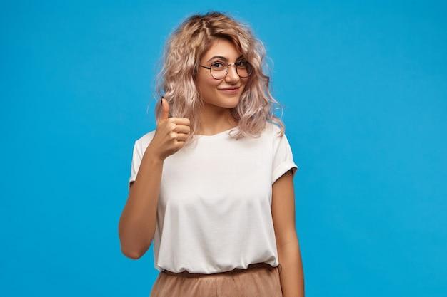 Foto de boa aparência, jovem e simpática mulher branca, vestindo roupas elegantes e óculos redondos, fazendo gesto de aprovação, mostrando o sinal de positivo para a câmera e sorrindo alegremente