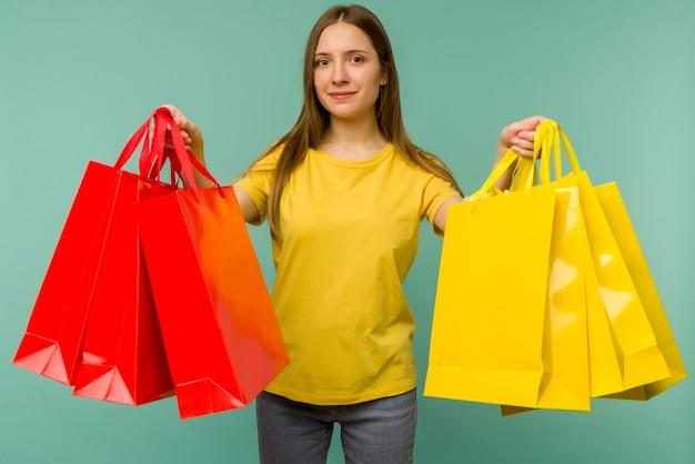 Foto de boa garota encantadora garota alegre atraente tendo acabado de fazer compras e ficar muito feliz e alegre enquanto com azul.