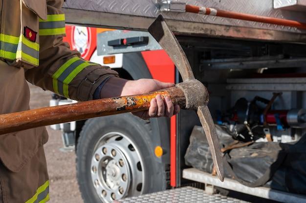 Foto de bombeiro com martelo contra máquina de fogo