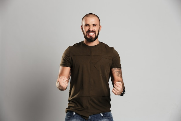 Foto de bonitão tatuado com barba e bigode, cerrando os punhos, mostrando a força, isolada sobre a parede cinza