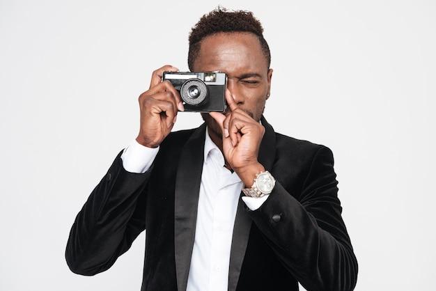Foto de bonito jovem empresário africano fazer uma foto com sua câmera. isolado sobre fundo branco.