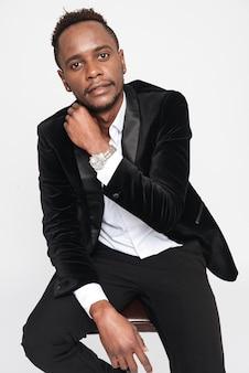Foto de bonito jovem empresário africano sentado no banquinho. isolado sobre fundo branco. olhe para a câmera.