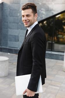 Foto de bonito jovem empresário caminhando ao ar livre na rua com o computador portátil.