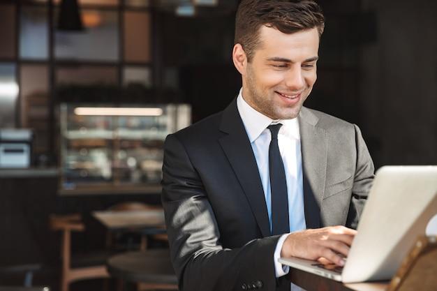 Foto de bonito jovem empresário com roupas formais dentro de casa no café, usando o computador portátil.