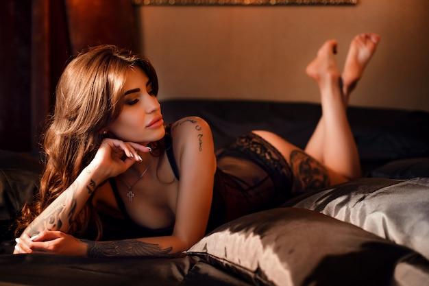 Foto de boudoir de garota sexy vestindo roupas íntimas elegantes posando no quarto.