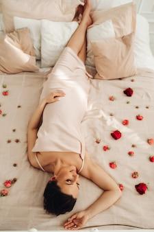 Foto de cabeça para baixo de uma mulher morena relaxada em um vestido bege deitada em uma cama polvilhada com pétalas de flores