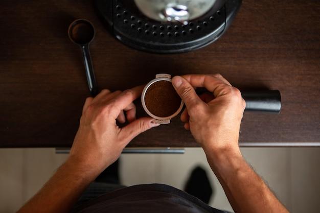Foto de cafeteira, mão de homem servindo café na cozinha