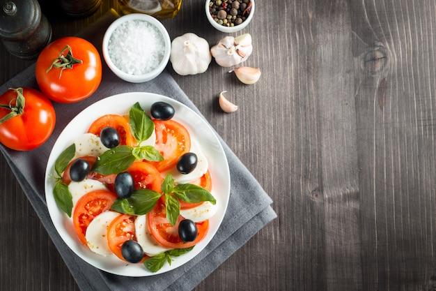 Foto de caprese salad com tomate, manjericão, mussarela, azeitonas e azeite no fundo de madeira. ingredientes da salada caprese tradicional italiana. conceito de comida mediterrânica, orgânica e natural.