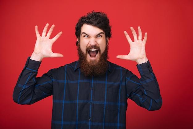 Foto de cara barbudo, fazendo uma cara assustadora e levantando as mãos sobre parede vermelha