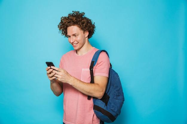 Foto de cara caucasiano hipster com cabelos cacheados, vestindo roupas casuais e mochila sorrindo e segurando o smartphone