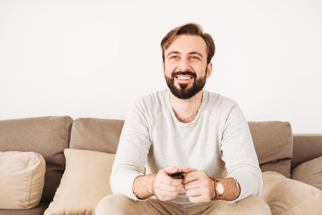 Foto de cara feliz, com barba e bigode, descansando em casa no sofá e assistindo tv com controle remoto nas mãos