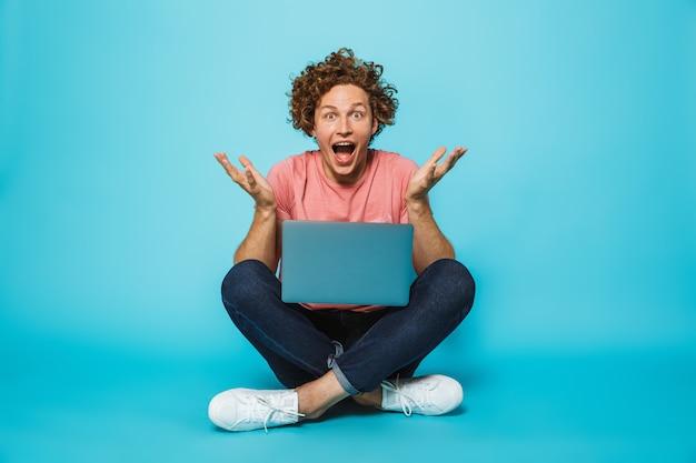 Foto de cara feliz surpresa com cabelos cacheados castanhos usando laptop prata, enquanto está sentado no chão com as pernas cruzadas
