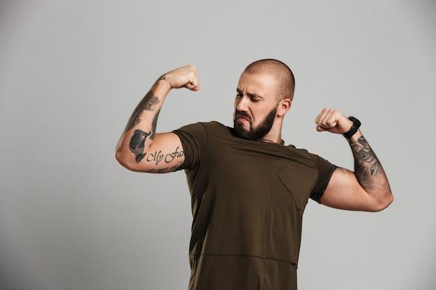 Foto de cara tatuado forte com barba e bigode mostrando seu bíceps, isolado sobre parede cinza