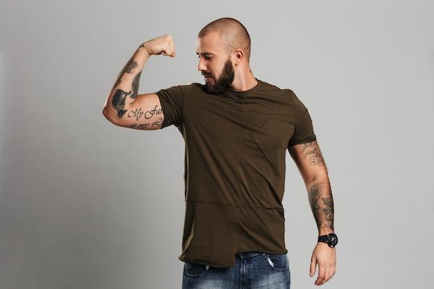 Foto de cara tatuado forte com barba e bigode, olhando para o bíceps, isolado sobre parede cinza