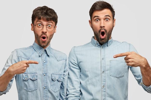 Foto de caras barbados espantados com expressão estupefata apontam um para o outro com o dedo indicador, usam camisas jeans, abrem bem a boca, encostam-se na parede branca. conceito de amizade