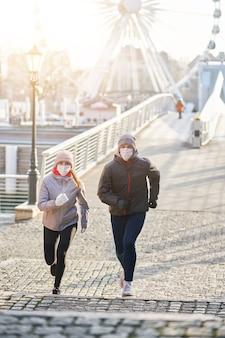 Foto de casal adulto correndo na cidade mascarado durante uma pandemia de bloqueio
