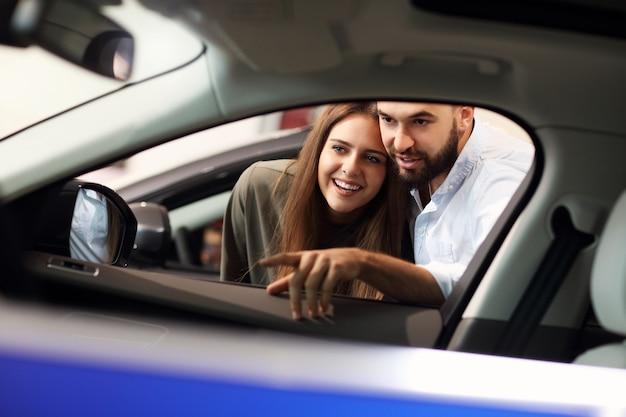 Foto de casal adulto escolhendo carro novo no showroom