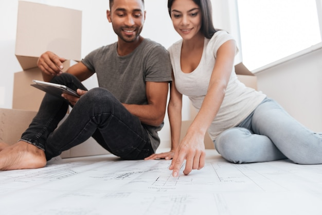 Foto de casal alegre, planejando a decoração da nova casa, sentada no chão. festa de inauguração.
